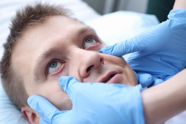患者の目の粘膜を検査する手袋をした医師。患者の意識概念の評価
