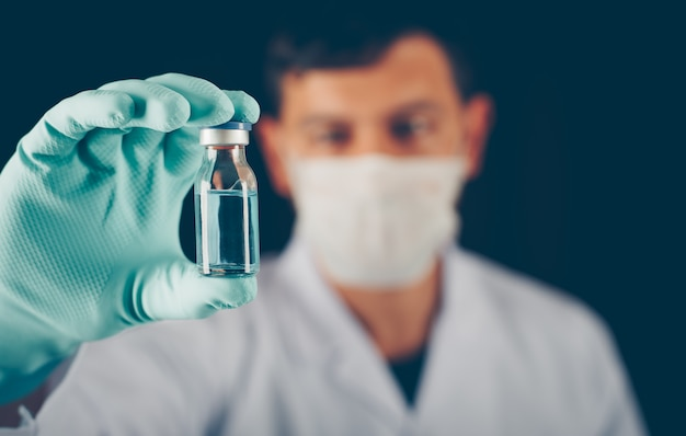 Doctor with gloves and mask holding vial in his hand close-up