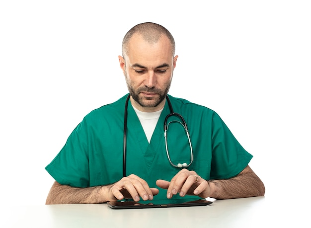 Doctor with green clothes uses a tablet sitting at a table.