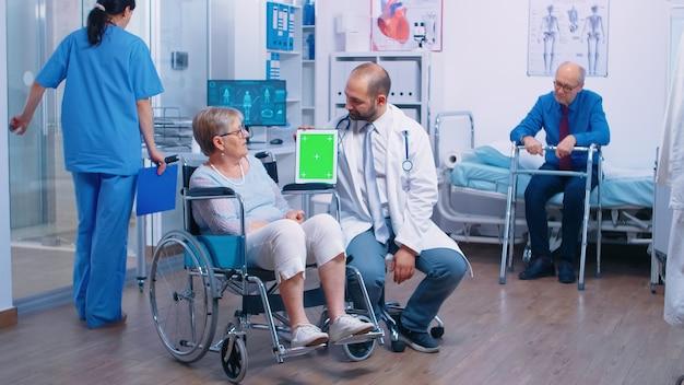 노인 장애인 환자를 위한 재활 센터에서 녹색 스크린 태블릿을 가진 의사. 앱, 텍스트, 비디오 또는 디지털 자산을 쉽게 대체할 수 있는 격리된 크로마 모형입니다. 건강 관리 의학 및 tr
