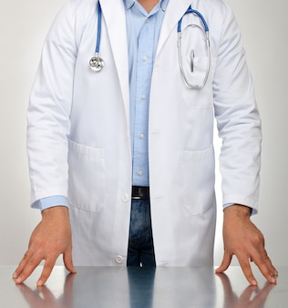 Doctor with hands resting on the table for examination