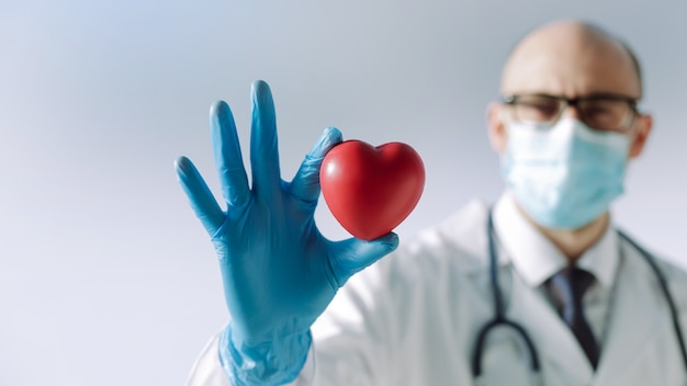 Doctor with a heart in his hands looking at you