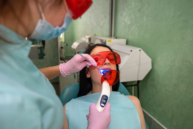 Doctor with lamp and mirror treating patients teeth close up