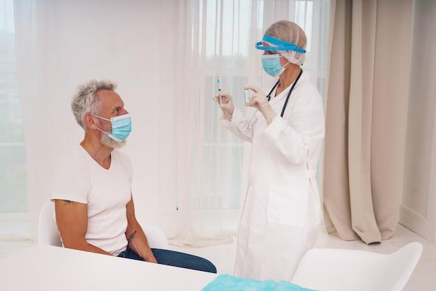 마스크와 주사기를 든 의사, 코로나 19 예방 접종 준비 완료