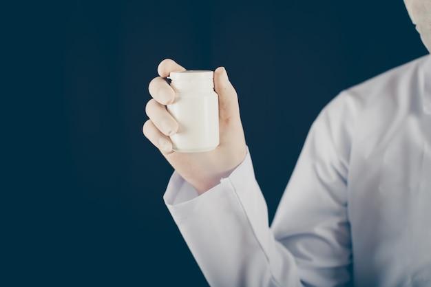 Medico con la maschera e guanti che tengono una pillola imbottiglia la sua vista laterale della mano