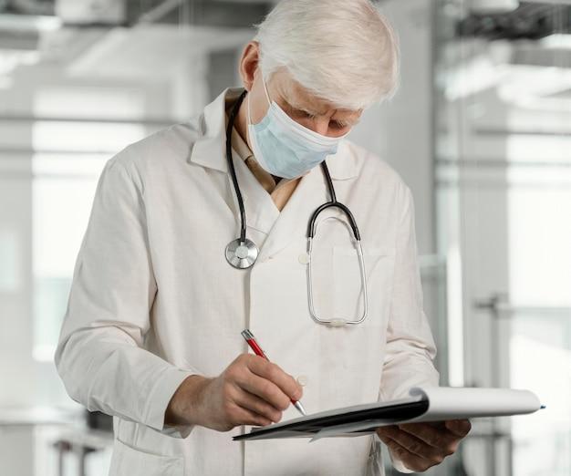 Medico con mascherina medica che controlla i suoi appunti