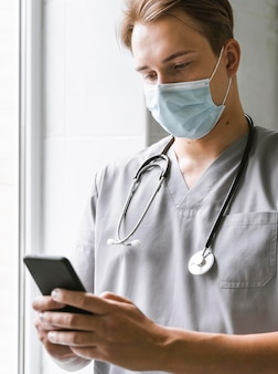 Doctor with medical mask checking smartphone