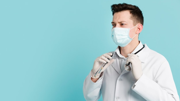 Doctor with medical mask holding his stethoscope