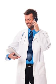Доктор с мобильным телефоном что-то проверяет на цифровом планшете