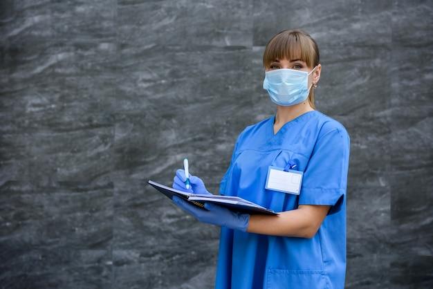 メモ帳を持つ医師。聴診器でマスクの灰色の背景にポーズをとる青い医療コートの女性