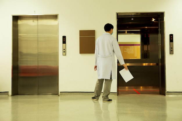 Doctor with paper report and open elevator