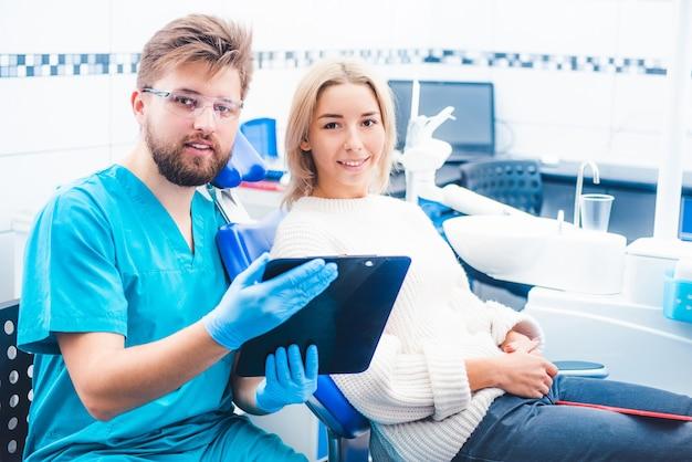 Врач с пациентом, читающий заметки из блокнота