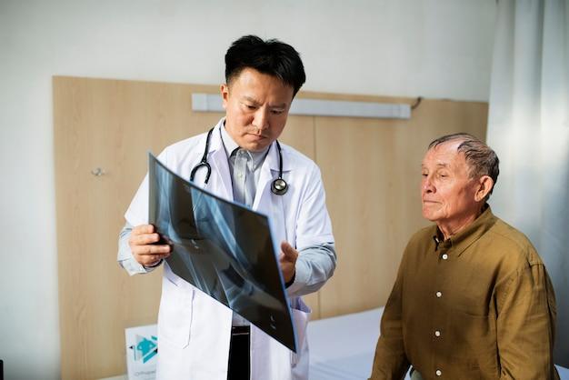 患者用レントゲンフィルムを持つ医師