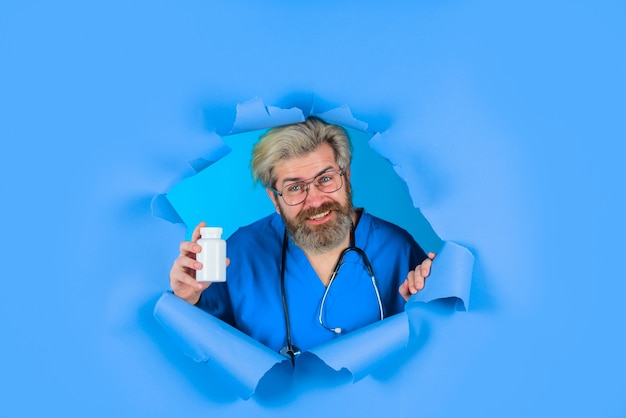 Doctor with pills pharmaceutical drug bearded doctor doctor with stethoscope holds pills through