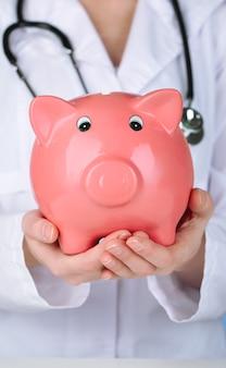 ピンクの貯金箱を持つ医者、クローズアップ
