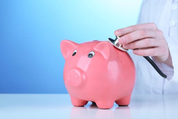 ピンクの貯金箱を持つ医者