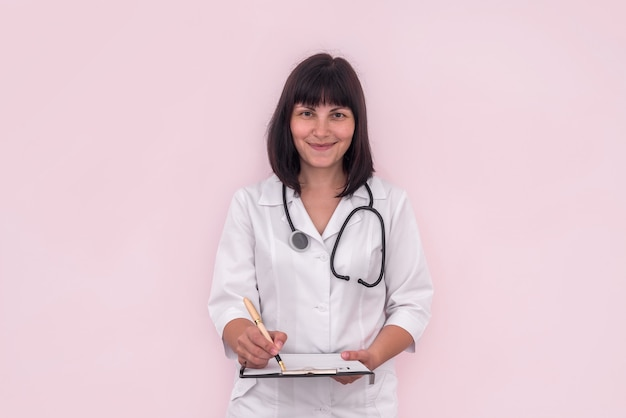ピンクで分離されたクリップボードの処方箋を持つ医師