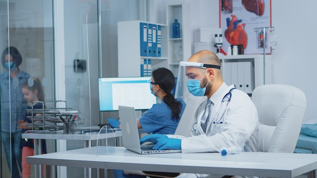 Doctor with protection mask and visor typing the treatment on laptop while mother comes with daughter to the consultation in hospital during coronavirus pandemic. equipped nurse talking with patients.