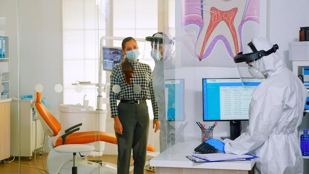 보호복을 입은 의사는 코로나바이러스 기간 동안 치아 검사를 위해 구강병실에 다음 환자를 초대합니다. 치과 진료소에서 전체, 안면 보호대, 마스크, 장갑을 끼고 있는 조수 및 치과 의사
