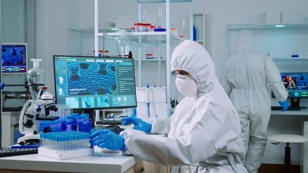 컴퓨터에 타이핑하는 실험실에서 혈액 샘플을 작업하는 보호복을 입은 의사. covid19 바이러스에 대한 치료 개발 연구를 위해 첨단 기술을 사용하여 백신 진화를 조사하는 화학자