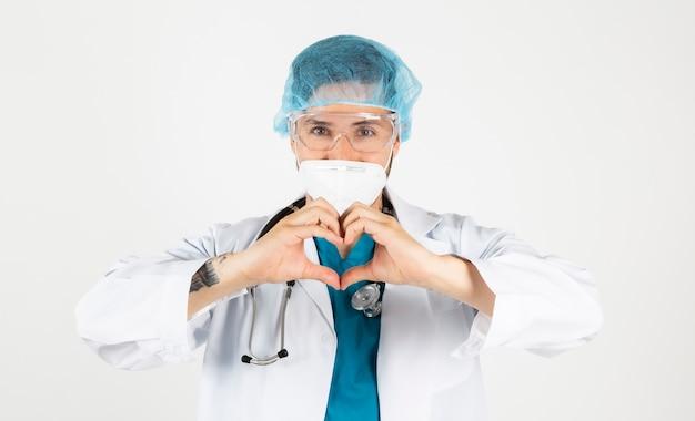 Врач в защитной маске, посвященный своим пациентам, на белом фоне