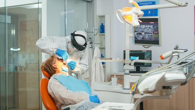 コロナウイルスのパンデミック時に滅菌歯科用ツールを使用して歯の衛生的なクリーニングを行う保護マスクを持った医師。口腔病クリニックでつなぎ服、フェイスシールド、マスク、手袋を着用した医療チーム