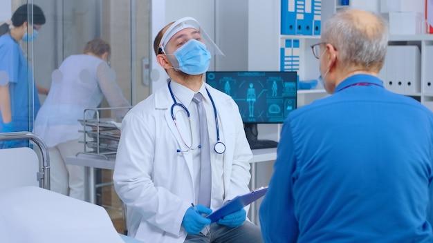 Врач в защитной одежде консультирует пожилого пациента во время covid 19. частная современная больница или клиника. запись на прием к врачу, вспышка коронавируса, защита от вирусов
