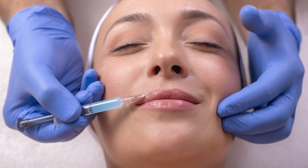 Medico con guanti di gomma che fa un intervento di plastica facciale su una giovane donna felice