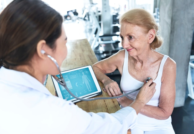 Doctor with senior woman in rehabilitation center check health care and showing data something on tablet.