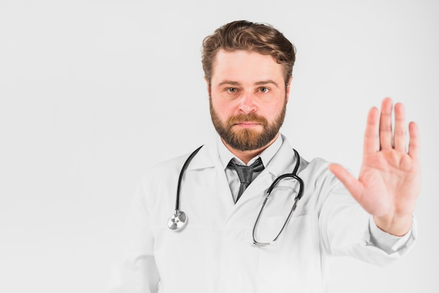 Doctor with serious face showing stop hand