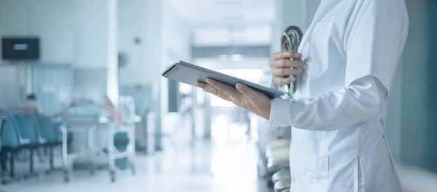 병원, 의료 및 의료 기술 개념에 태블릿에 환자 데이터를 분석하는 청진 기와 의사.