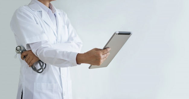 Doctor with stethoscope analyzing patient data on tablet, healthcare and medical technology concept.