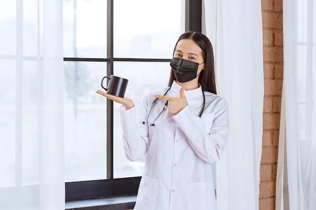 聴診器と黒いマスクを持った医師が休憩時間に黒い飲み物を持っています。