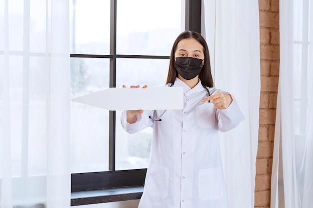聴診器と左向きの白い矢印を保持している黒いマスクを持つ医師。