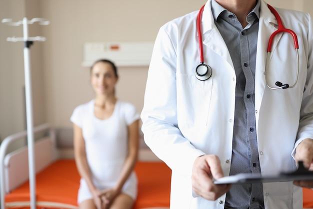女性患者のクローズアップで病棟に立っている彼の手で聴診器とドキュメントを持つ医師
