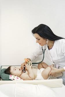 聴診器を持つ医師。服のない赤ちゃん。医師による診察。