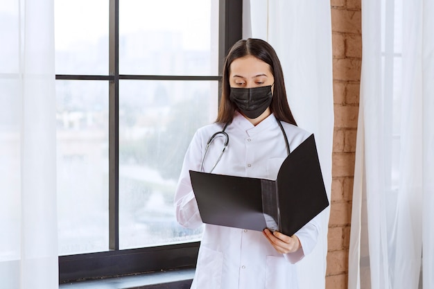 Doctor with stethoscope and black mask standing next to the window and holding a black history folder of the patients, opening and reading them.