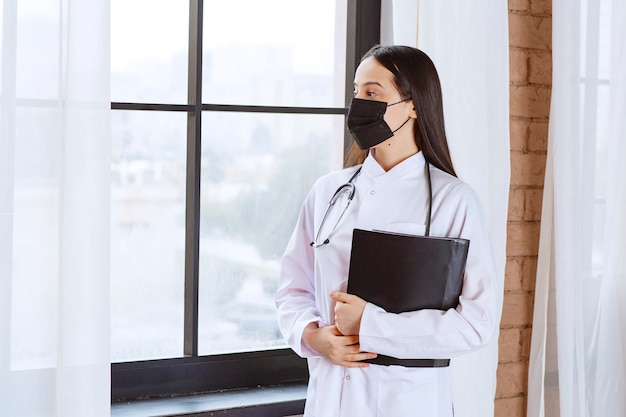 Medico con lo stetoscopio e la maschera nera in piedi accanto alla finestra e che tiene in mano una cartella nera della storia dei pazienti mentre guarda attraverso la finestra.