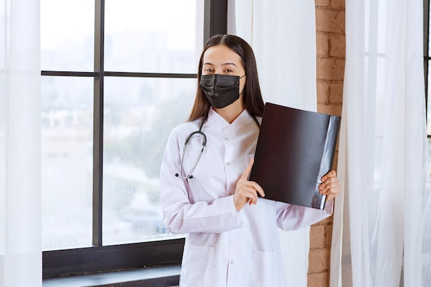 Doctor with stethoscope and black mask standing next to the window and holding a black history folder of the patients.