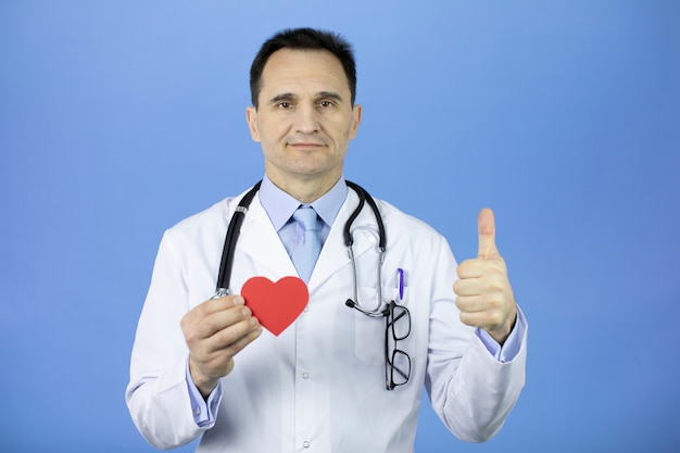 Doctor with a stethoscope on bright blue  holds a heart in his hand and shows a like.
