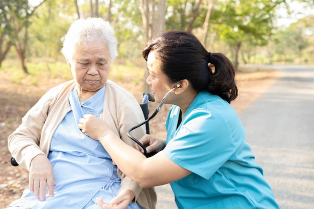 Doctor with stethoscope checking senior lady patient while sitting on wheelchair in park.