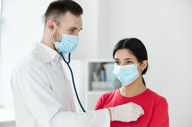 Doctor with a stethoscope examines a patient wearing a medical mask breathing lungs health.