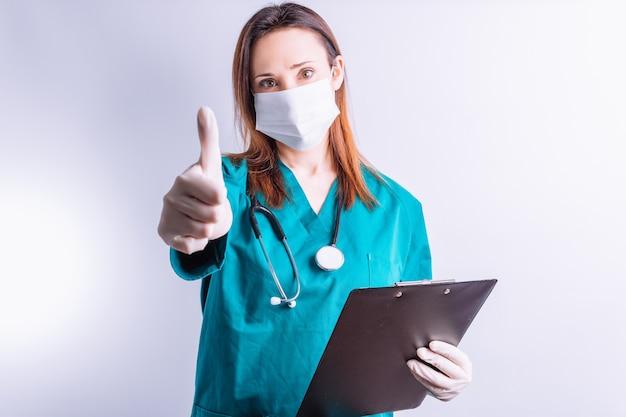 聴診器のフェイスマスクを持った医師は、大丈夫であることの象徴として親指を上げると報告しています。医学の概念