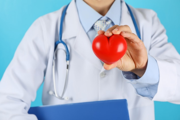 Doctor with stethoscope and heart against blue surface close up