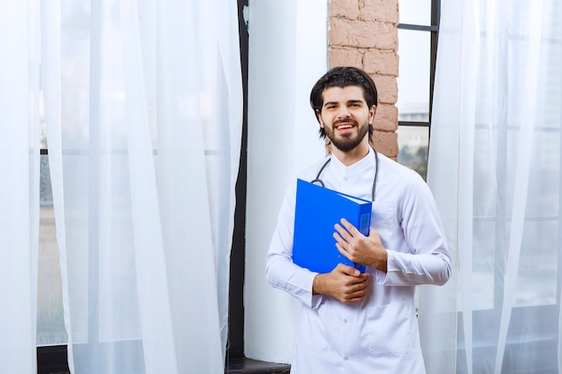 Doctor with a stethoscope holding a blue reporting folder.
