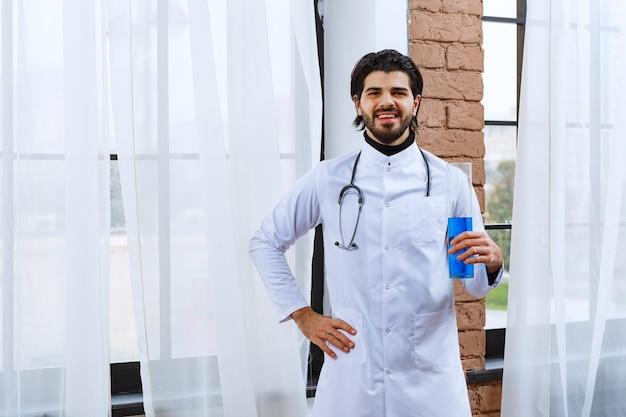 Medico con uno stetoscopio che tiene un pallone chimico con liquido blu all'interno.