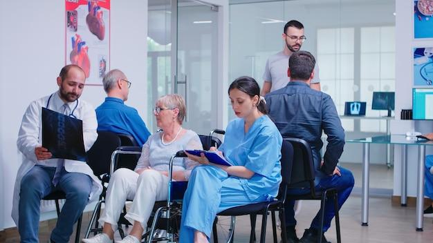 Врач со стетоскопом, держащий рентгенографию пожилой женщины-инвалида в инвалидной коляске, разговаривает с ней в зоне ожидания больницы. пациент спрашивает о назначении на прием в клинике.