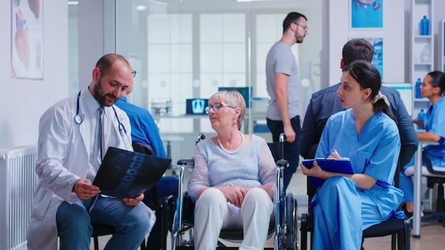 病院の待合室で彼女と話している間、車椅子で障害のある年配の女性のレントゲン写真を保持している聴診器を持つ医師。クリニックの受付で自分の割り当てについて尋ねる患者。