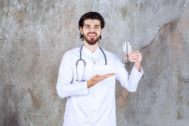 Dottore con uno stetoscopio che tiene in mano un bicchiere di acqua pura e indica da qualche parte