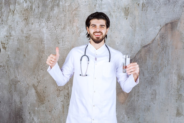 Doctor with a stethoscope holding a glass of pure water and showing positive hand sign.